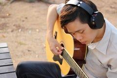 De selectieve nadruk van de jonge ontspannen mens speelt akoestische gitaar in openlucht Stock Foto