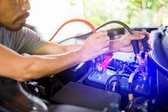 De selectieve nadrukhanden doen het laden autobatterij met elektriciteit door kabels van van andere auto stock fotografie