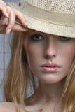 De sensuele blonde vrouw tuurt uit van onder de rand Royalty-vrije Stock Afbeelding