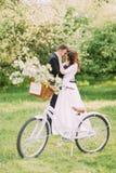 De sensuele jonge holding van het jonggehuwdepaar elkaar in park Fiets met huwelijksdecoratie op voorgrond royalty-vrije stock foto