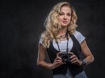 De sensuele krullende fotograaf van het blondemeisje gekleed in een wit t-shirt en een vest draagt heel wat toebehoren en royalty-vrije stock foto's