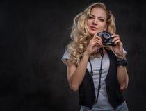 De sensuele krullende fotograaf van het blondemeisje gekleed in een wit t-shirt en een vest draagt heel wat toebehoren en royalty-vrije stock afbeelding