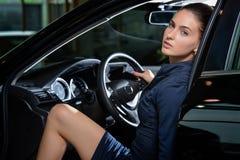 De sensuele ontspannen zitting van de vrouwenbestuurder binnen haar auto Stock Afbeeldingen