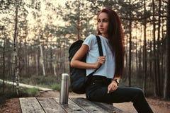 De sensuele zitting van het toeristenmeisje op een houten lijst, die onderbreking in een mooi de herfstbos hebben bij zonsonderga stock fotografie