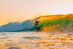 8 de septiembre de 2018 Bali, Indonesia Paseo de la persona que practica surf en onda del barril en la puesta del sol caliente El foto de archivo libre de regalías