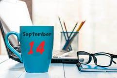 14 de septiembre Día 14 del mes, color azul de la taza de café de la mañana con el calendario en fondo del lugar de trabajo del i Fotos de archivo libres de regalías
