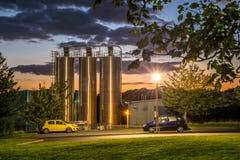 25 de septiembre de 2015, silos de la fábrica más allá del aparcamiento de los trabajadores en la puesta del sol Foto de archivo