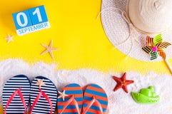 1 de septiembre Imagen del 1 de septiembre, calendario en fondo amarillo del verano con los accesorios de las vacaciones de la pl Foto de archivo libre de regalías