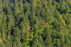 14 de septiembre de 2018 - Juneau, Alaska: Dos coches y árboles rojos de Robert Tramway del soporte foto de archivo