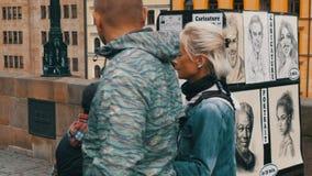 12 de septiembre de 2017 - Praga, República Checa: El artista de la calle pinta un retrato de una mujer hermosa joven en Charles almacen de video