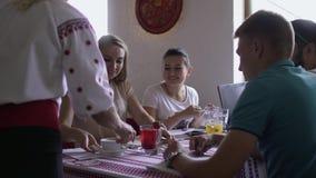 De serveerster brengt dranken aan jong bedrijf van mensen in koffie stock video