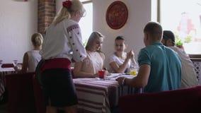 De serveerster brengt dranken te het bestuderen van studenten in koffie stock footage