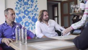 De serveerster brengt fles wijn voor bedrijf van zakenlieden in restaurant stock video