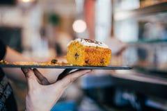 De serveerster draagt heerlijke zoete wortelcake royalty-vrije stock foto's