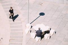 De serveerster komt aan de lijst waarbij een mens zit Stree Stock Foto