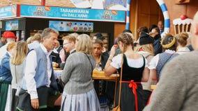 17 de setembro de 2017 - Munich, Alemanha: Os povos descansam, cerveja da bebida em tabelas da rua em Theresienwiese, Oktoberfest filme