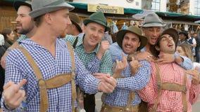 17 de setembro de 2017 - Oktoberfest, Munich, Alemanha: A empresa alegre de jovens no Bavarian nacional sere Lederhose vídeos de arquivo
