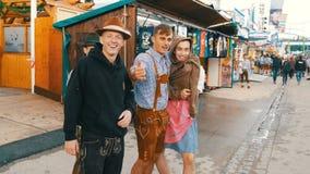 17 de setembro de 2017 - Oktoberfest, Munich, Alemanha: A empresa alegre de jovens no Bavarian nacional sere Lederhose video estoque
