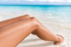 De sexy benen die van de bruine kleur skincare bikini op strand ontspannen royalty-vrije stock afbeeldingen