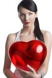 De sexy brunette met hart gevormde ballon kijkt binnen aan de lens Royalty-vrije Stock Foto's