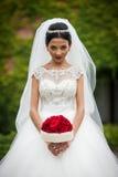 De sexy donkerbruine bruid in uitstekende modieuze witte kleding met rood nam toe Stock Afbeelding