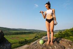 De sexy donkerbruine instructeur die van de vrouwengeschiktheid oefeningen met domoren en bal doen Openlucht opleidingsconcept Gr Stock Foto's