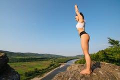 De sexy donkerbruine instructeur van de vrouwengeschiktheid met zich het perfecte spierlichaam openlucht uitrekken Groen bergenla Stock Afbeelding