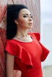 De sexy donkerbruine vrouw in een rode kleding bevindt zich dichtbij de rode poort Royalty-vrije Stock Fotografie