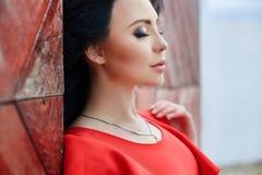 De sexy donkerbruine vrouw in een rode kleding bevindt zich dichtbij de rode poort Stock Foto