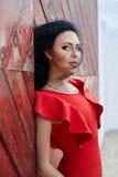 De sexy donkerbruine vrouw in een rode kleding bevindt zich dichtbij de rode poort Stock Fotografie