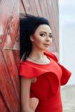 De sexy donkerbruine vrouw in een rode kleding bevindt zich dichtbij de rode poort Royalty-vrije Stock Foto