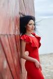 De sexy donkerbruine vrouw in een rode kleding bevindt zich dichtbij de rode poort Stock Afbeelding