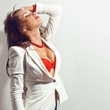 De sexy donkerbruine vrouw raakt haar haar over witte muur Stock Afbeelding