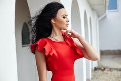 De sexy donkerbruine vrouw in rode kleding bevindt zich dichtbij de muren van ol Stock Foto's