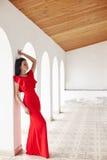De sexy donkerbruine vrouw in rode kleding bevindt zich dichtbij de muren van ol Royalty-vrije Stock Fotografie