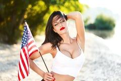 De sexy donkerbruine vrouwenholding de V.S. markeert openlucht Stock Foto's