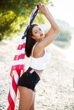 De sexy donkerbruine vrouwenholding de V.S. markeert openlucht Stock Fotografie