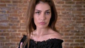 De sexy gedeprimeerde vrouw let op bij camera, baksteenachtergrond stock footage