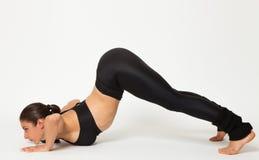 De sexy geschikte donkerbruine vrouw in sportenslijtage in yoga stelt Stock Foto's