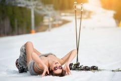 De sexy glimlachende vrouwelijke skiër ligt op sneeuwhelling onder skilift stock afbeeldingen