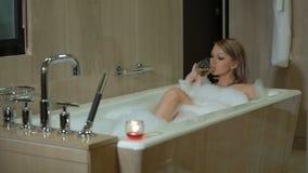 De sexy jonge blondevrouw neemt schuimend bad, ontspant en geniet, drinkt van witte wijn, binnen drinkt het meisje champagne stock video