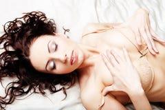De sexy jonge vrouw stelt op bed Stock Afbeeldingen