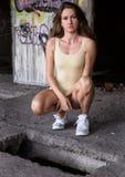 De sexy jonge vrouw in zwempak hurkt naast het gat in de vloer in de verlaten bouw royalty-vrije stock foto
