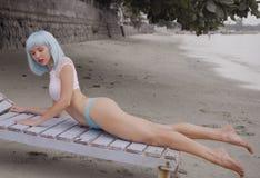 De sexy mooie vrouw in het moderne futuristische stijl stellen op het beschadigde houten blauw sunbed royalty-vrije stock fotografie