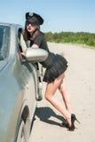 De sexy politievrouw op weg houdt auto tegen Stock Foto's