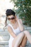 De sexy slanke witte kleding en de zonnebril van de dameslijtage vast plotseling stock foto