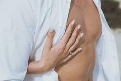 De sexy spier naakte mens en de vrouwelijke handen gespen zijn jeans los Royalty-vrije Stock Foto's