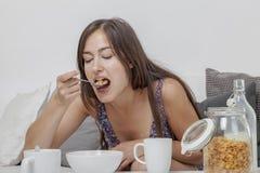 De sexy student in nachttoga heeft ontbijt op de bank Stock Fotografie