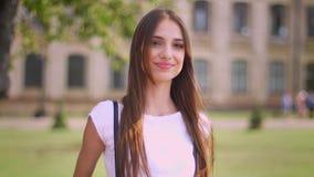 De sexy vrouw bevindt zich in park in dag, lettend op rond en bij camera, het glimlachen, de vage bouw op achtergrond stock videobeelden