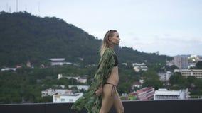 De sexy vrouw die van de blondeglamour zwart swimwear en bloemen lang overhemd dragen die op een dak in een zonnige de zomerdag l stock video